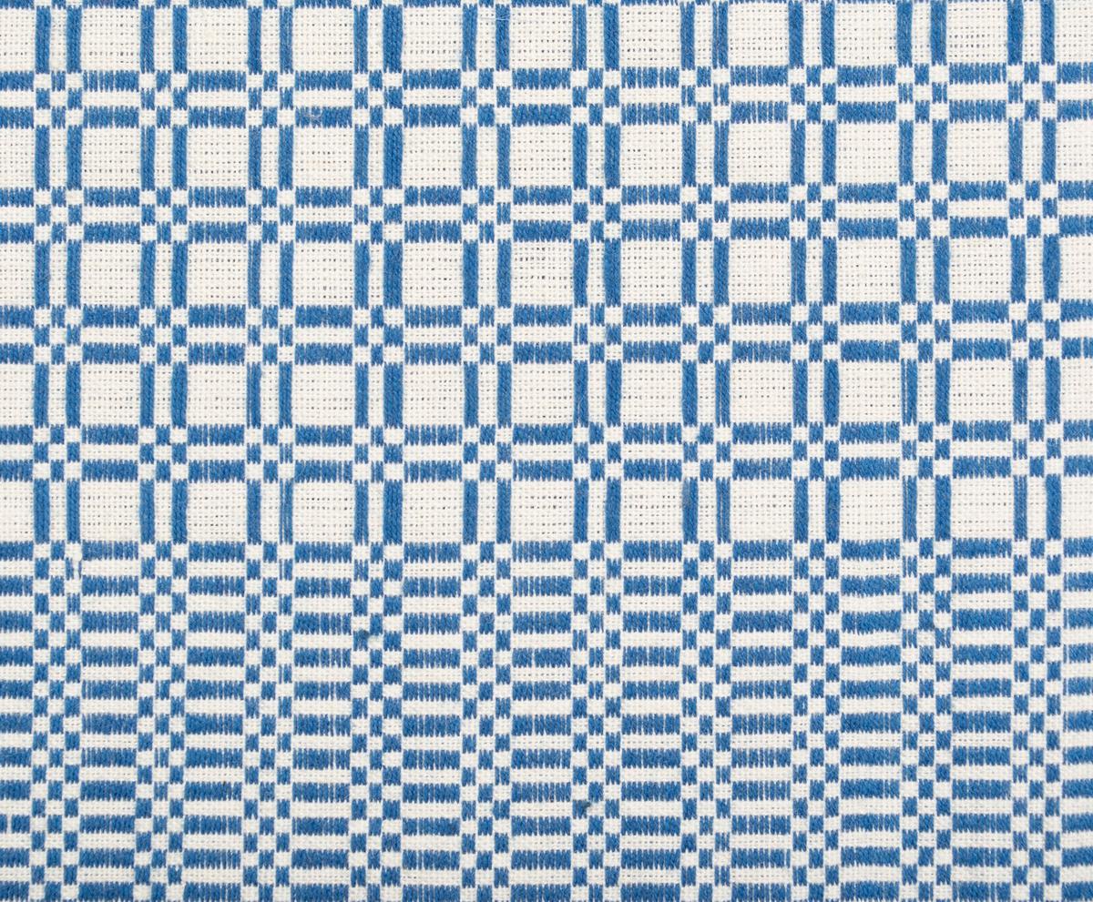 """Vävprov i plattväv. Yttäckande, smårutigt mönster i bård och mittfält. Blått mönster på vit/oblekt botten. 75-80 mm bred bård. Varp i 2-trådigt bomullsgarn, 22 trådar/cm. Inslag i 2-trådigt s-tvinnat bomullsgarn, 18 inslag/cm.Stadkant i en sida langettkantning på tre sidor. Påsydd tyglapp från Malmöhus Läns Hemslöjdsförening med texten: """" Litt. H.  Modell N:o 5.""""."""