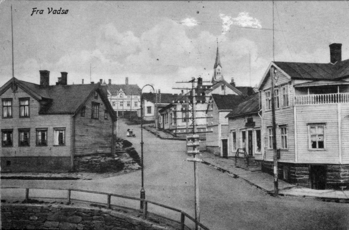 Postkort fra Vadsø - Tollbodgaten fotografert fra krysset med Havnegata og oppover mot Fylkesgården. Til venstre Peder L. Persens bolighus som i 1935 ble løftet opp og ny sokkeletasje bygget på, dit Vadsø ekviperingsforretning flyttet i 1942. Huset med trapp på høyre siden av veien var Kildahl Olsens bokhandel. Det lyse huset helt til høyre var Kildahl Olsens bolig. I kjelleretasjen var det i midten av 1920-årene en fiskematbutikk og senere en slaktebutikk. Denne bygningen ble senere kjøpt av skattefogd Trasti, og skattefogkontoret ble flyttet til de tidligere bokhandel-lokalene