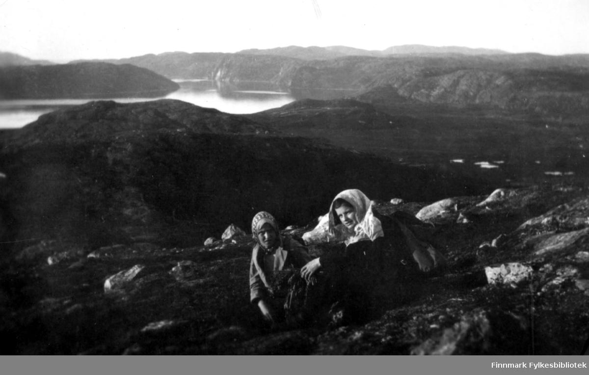 Ruth Grønvigh og Solveig Evanger tar en hvilepause med utsikt over Bugøyfjord, sommeren 1934. De var ille plaget av mygg på turen.