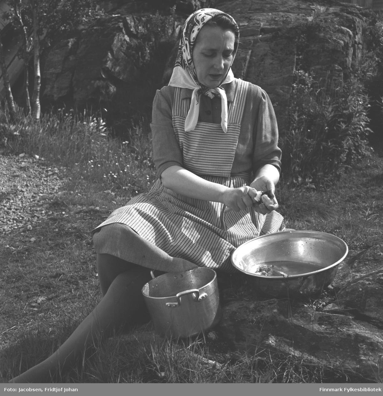 Aase Randi Jacobsen sitter i foreldrenes hage og skreller potet.