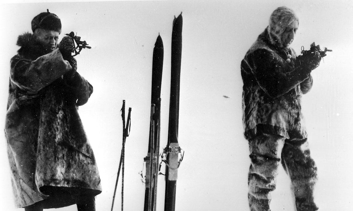 To personer. to par ski oppreist i snøen ved siden av.