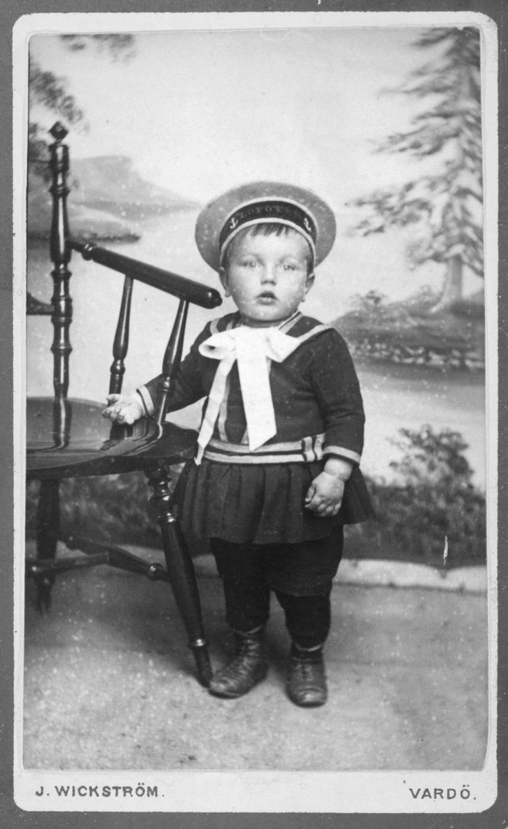 """Portrett helfigur av liten gutt i matrosdress med matroshatt. """"Lofoten"""" står det på matrosluen. Gutten er Albert Ballo, født 13.07.1876, fotografert i Vardø av fotograf Johan Erik Wickstrøm i perioden 1879-1880. På bildet er han ca. 3 år gammel. Fotograf Wickstrøm, født i Happaranda i 183, hadde yrke som """"fotograf og tolk i det svænske og lapiske sprog"""". Han holdt til i Tromsø i 1875 på adresse Westre Gade 389.   Albert Ballo er senere registrert i folketellingen for 1910, for Nord-Varanger herred, som fisker og jordbruker.  Ref. også bildeFBib.05021-017 som er en variant av dette bildet. Albert Ballo er også registrert som """"Hjemvendt norsk-amerikaner, utflyttet: 1900 og tilbakeflyttet: 1907. Siste bosted i Amerika var Milvauki (Milwaukee, Wisconsin, Usa). Stilling i Amerkia: Grubearbeider."""" Hans mor er Emilie Ballo, født 03.06.1879 i Karjel, Nord-Varanger. Hun var født Wickstrøm. Hun er regisrert i 1910 som """"Hjemvendt norsk-amerikaner"""" fra 1902-1907 med stilling: Vaskerske."""""""