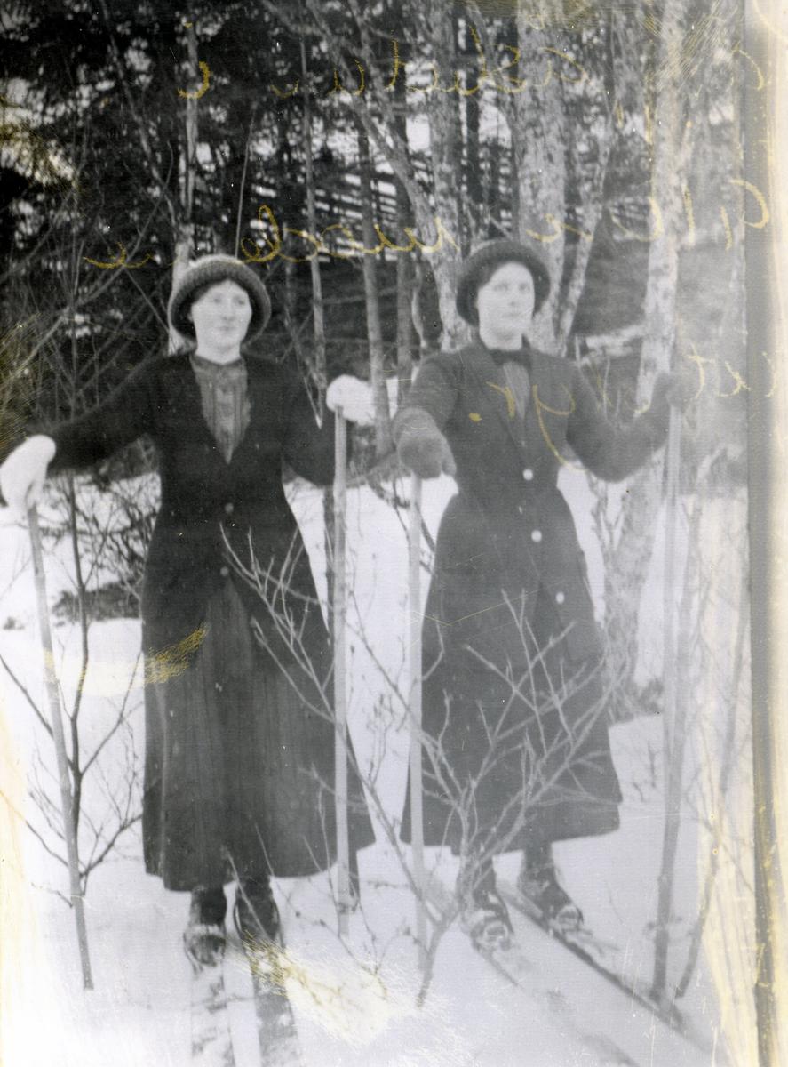 To kvinner på ski, kledd i lange kjoler (stakker) og side formsydde jakker