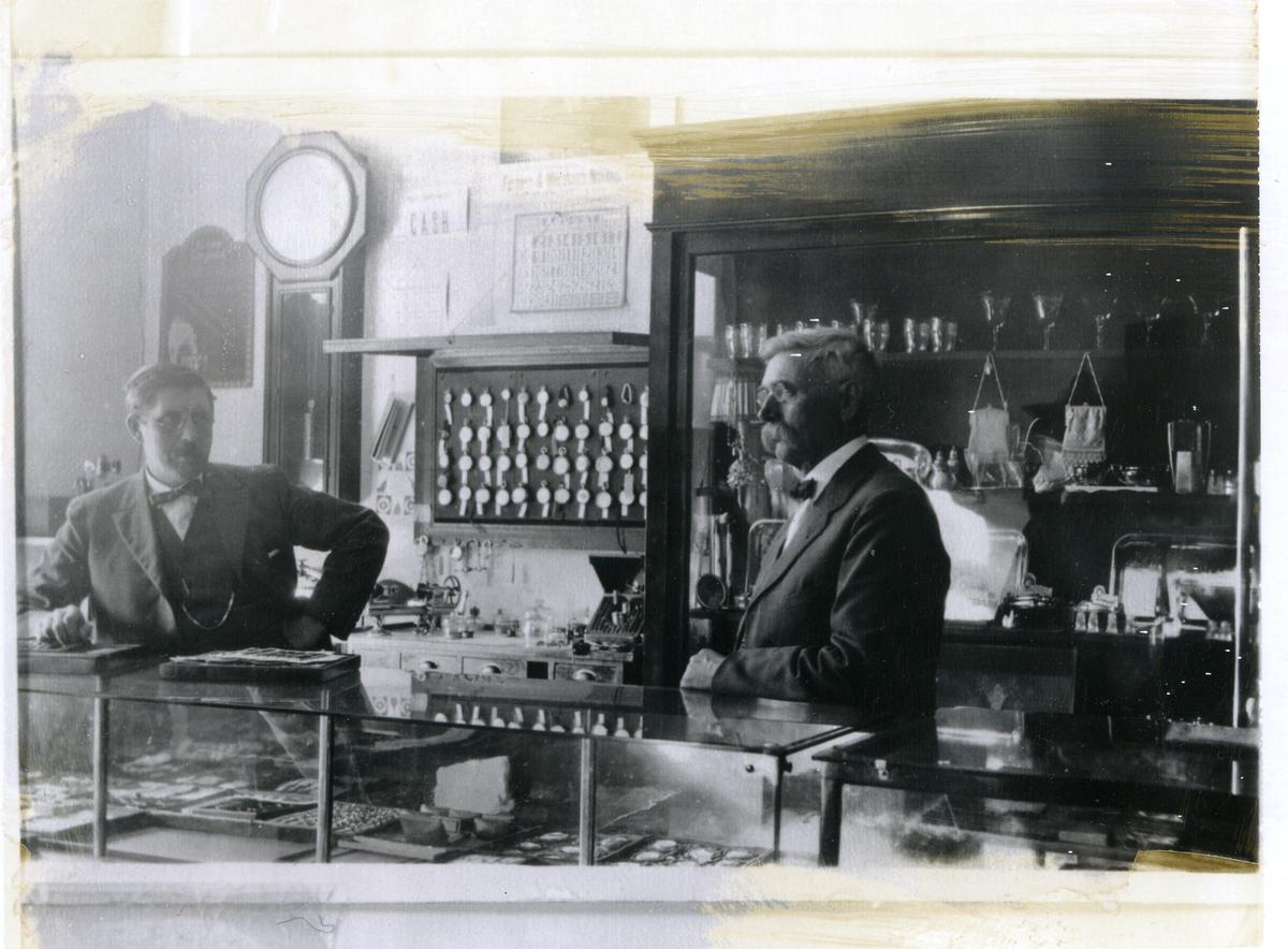To menn bak disken i Ola (Ole) O. Bang sin gullsmed- og urmakarforretning i USA. Til høgre Thore G. Skaret frå Reinli