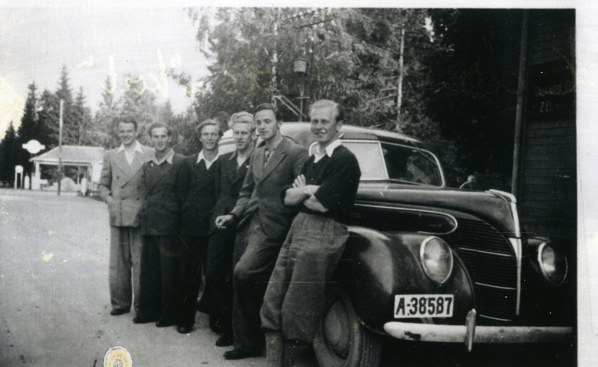 Seks unge menn framfor bil, fotografert på på Dokka på veg til kretsmesterskap i friidrett på Lunner. Bensinstasjon i bakgrunnen