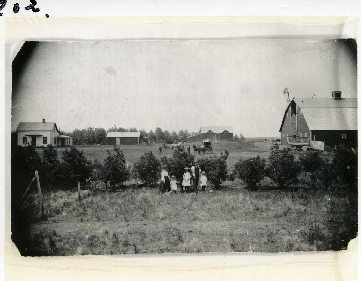 Bildet viser farmen til C. Melby i USA. Født ca 1850. Kona var fra Stokkebryn i Skrautvål. Familien foran og gårdshusene i bakgrunnen. Her er også flere hester og karjoler og en sykkel.