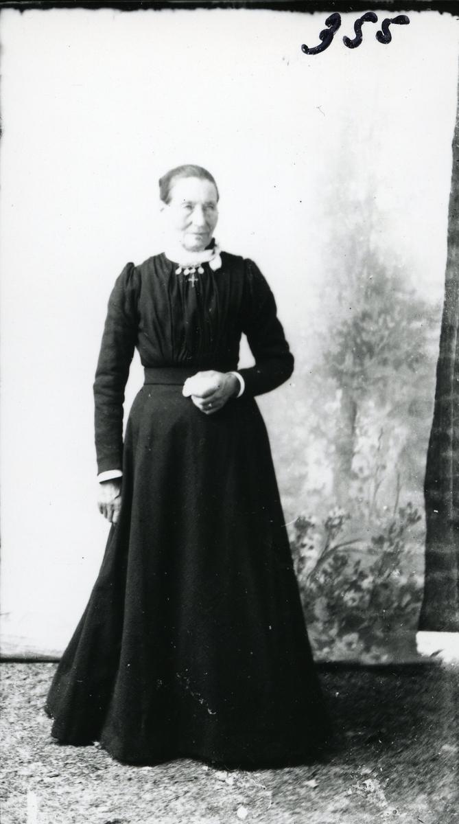 Portrett i helfigur av Marit Ferden, født Røn. Avbildet foran lerret i lang, svart kjole.