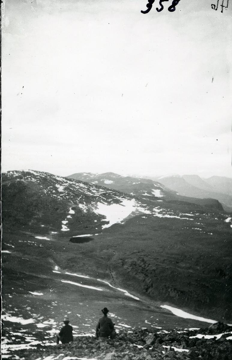 To menn sitter og skuer ut over fjellheimen. Begge med hatt. Foto tatt med Skogshorn (Hemsedal) i ryggen og med utsyn over Vangsfjella. Ranastonge, Rankonøse og Grindadn lengst bort.