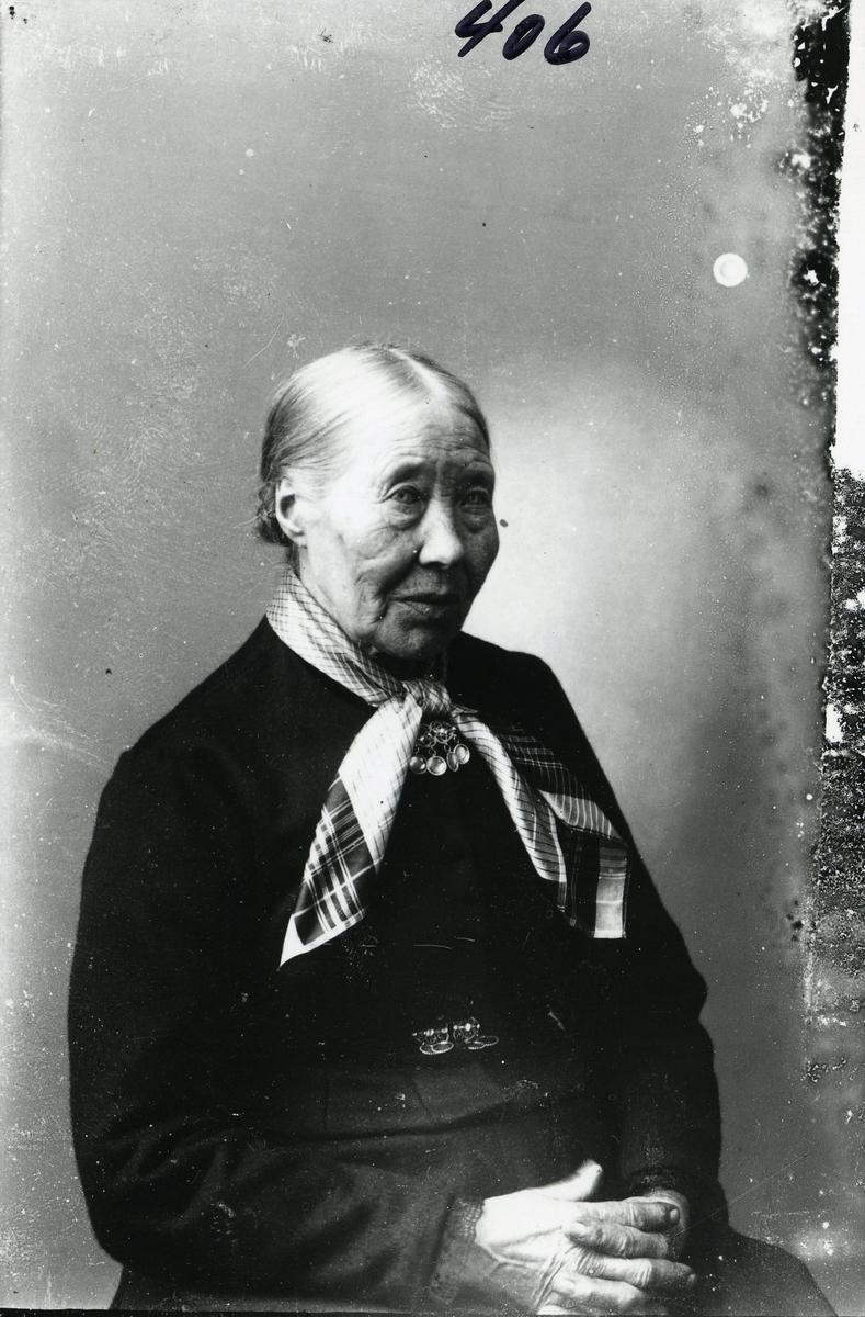 Kvinne i halvfigur avbildet foran lerret. Mørk stakk og bluse. Silkesjerf og sølje
