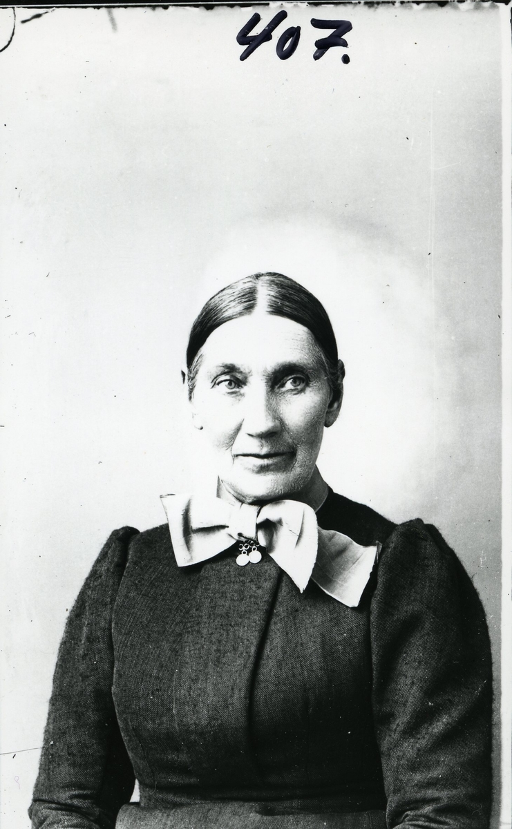 Kvinne i halvfigur avbildet foran lerret. Mørk kjole. Sølje og sløyfe i halsen.