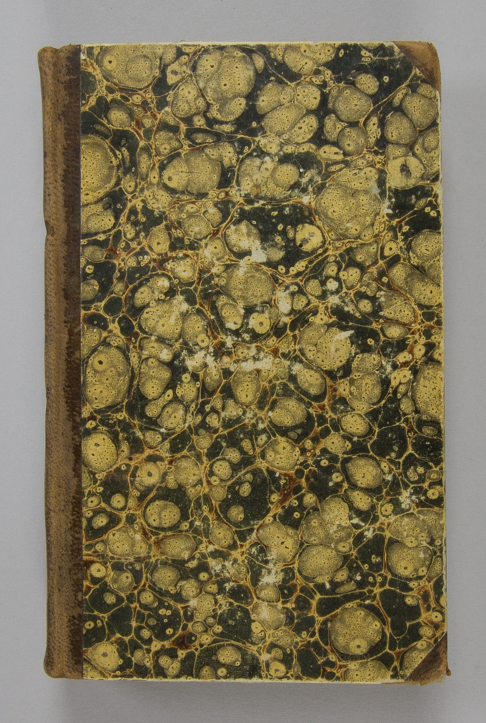 """Bok, halvfranskt band, innehållande två arbeten: """"Fönster-trädgården"""" och """"Berättelse om de arbeten och försök, som blifvit verkställde vid kongl. Landtbruks-academiens experimental-fält år 1827"""". Bandet med blindpressad och guldornerad rygg. Ryggen något blekt och skinnet ställvis ytligt nött. Pärmen klädd i marmorerat papper. Framsidans innerpärm med handskrivna titlar i bläck."""