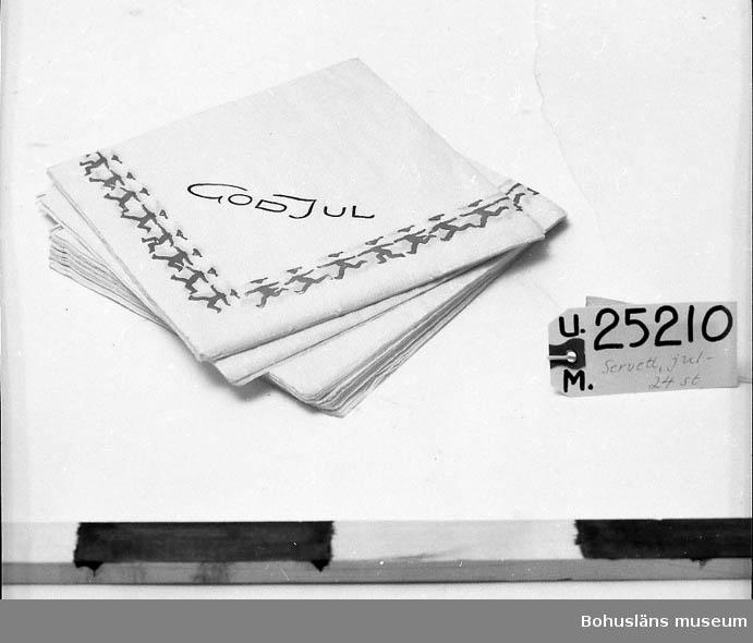 """471 Tillverkningstid 1940-55 410 Mått/Vikt !L:18.2, B:18 CM 601 Vita. Röd bård i form av tomtenissar. Grön text:""""GOD JUL"""". 602 Köpta i gammal lanthandel i Röra socken. Museet har tidigare gåvor 603 från samma affär. 604 Då servetterna skänktes till affären var det delar av ett plastomslag 605 runt om dem. På omslaget var det en vit klisteretikett med handskriven 606 text:""""1.50""""."""