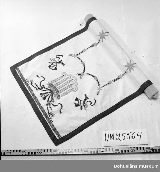 Broderad rektangulär  julduk. Bomullsgarn i grönt, gult, blått, orange mot vit botten. I varje kortända borderad med fem tända ljus och tre klockor. I mitten rektangulärt fält av stjärnor och granris. Kantad med 4 cm bred röd bomullsbård. Systrarna Elsa och Gunhild Ahlberg var översköterskor på S:t Jörgens mentalsjukhus och döttrar till Anders Ahlberg, trädgårdsmästare där 1880 - 1913. Mostrar till givaren. De bodde under yrkeslivet inom sjukhusområdet. Elsa Ahlberg handarbetade inte själv men förvärvade handarbeten av patienterna som ofta var sysselsatta med sådant.