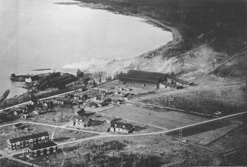 Wargöns AB. Wargöns anläggningar i Porjus. Smältverk uppfört 1916 till vänster och masugn uppförd 1917-19 till höger. Aero materiel AB flygfoto nr F 967. Foto ca 1930-tal.  Masugnen lades ner redan 1921. Smältverket var igång fram till 1958, då verket lades ned och revs. 1946 dämdes Porjusselet upp, och smältverket flyttades då upp till området där masugnsverket tidigare stått.