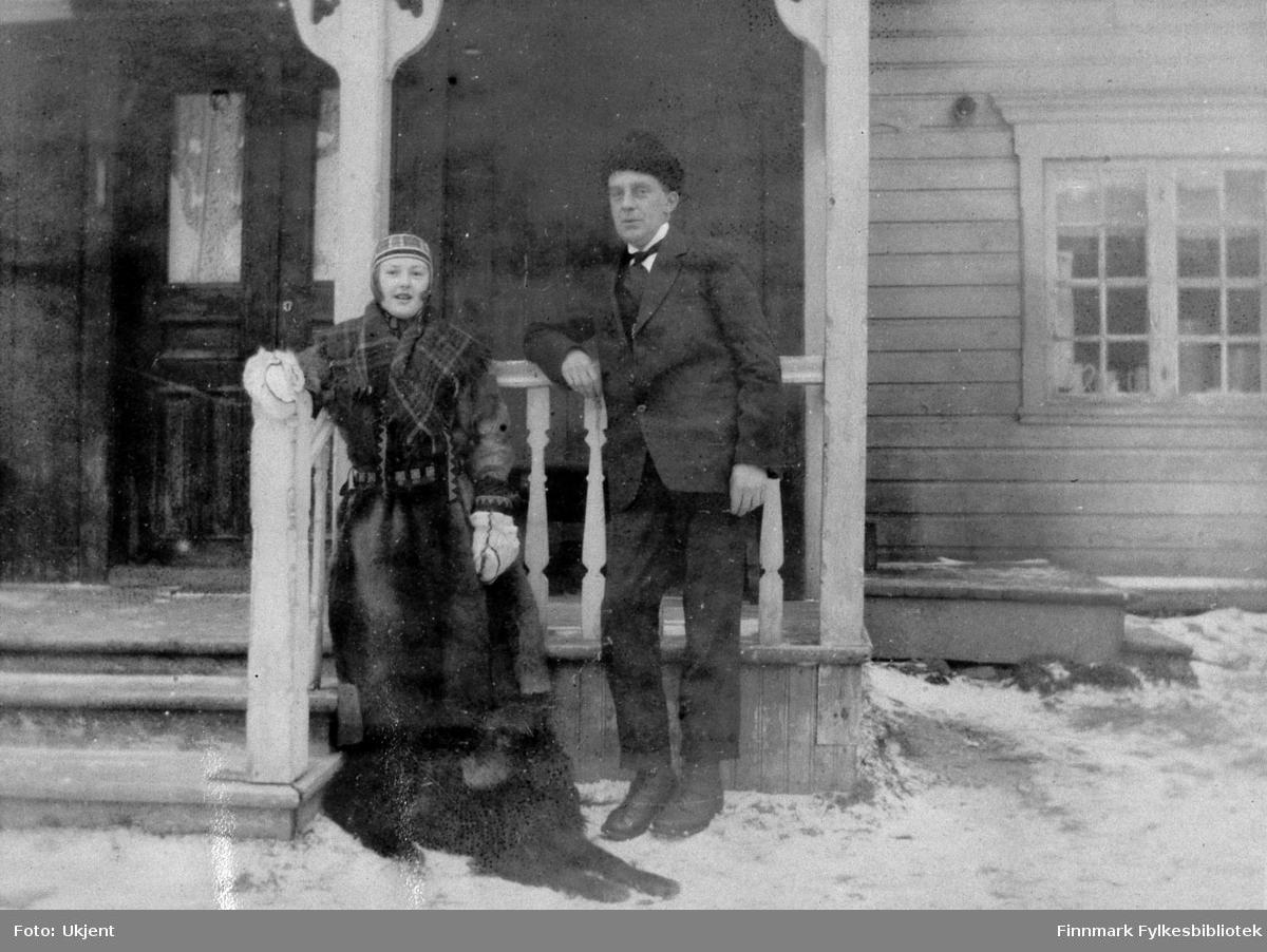 Bildet er tatt fra gården Strømsnes i Jarfjord en vinter mellom 1920-1925. Mannen og kvinnen i bildet er ukjente, men hunden som ligger på bakken er trolig Bertelsen familiens hund 'Tussemann'. Paret står ved siden av inngangspartiet av huset og man kan se at trappen er omringet av dekorative søyler. Trappen leder opp til en dør og til høyre kan man se et vindu. I vinduet kan man se enkelte gjenstander der i blant kanner og muligens kopper. Vinduet har gardiner i. På bakken kan man se snø. Kvinnen har på seg noe som kan minne om samiske klær. Hun har på seg en lue og en kåpe trolig laget av reinskinn. Hun har et rutete sjal rundt skuldrene og på hendene har hun tykke votter. Rundt livet har hun et belte. Mannen ved siden av har på seg lue, jakke, slips, bukser og sko.