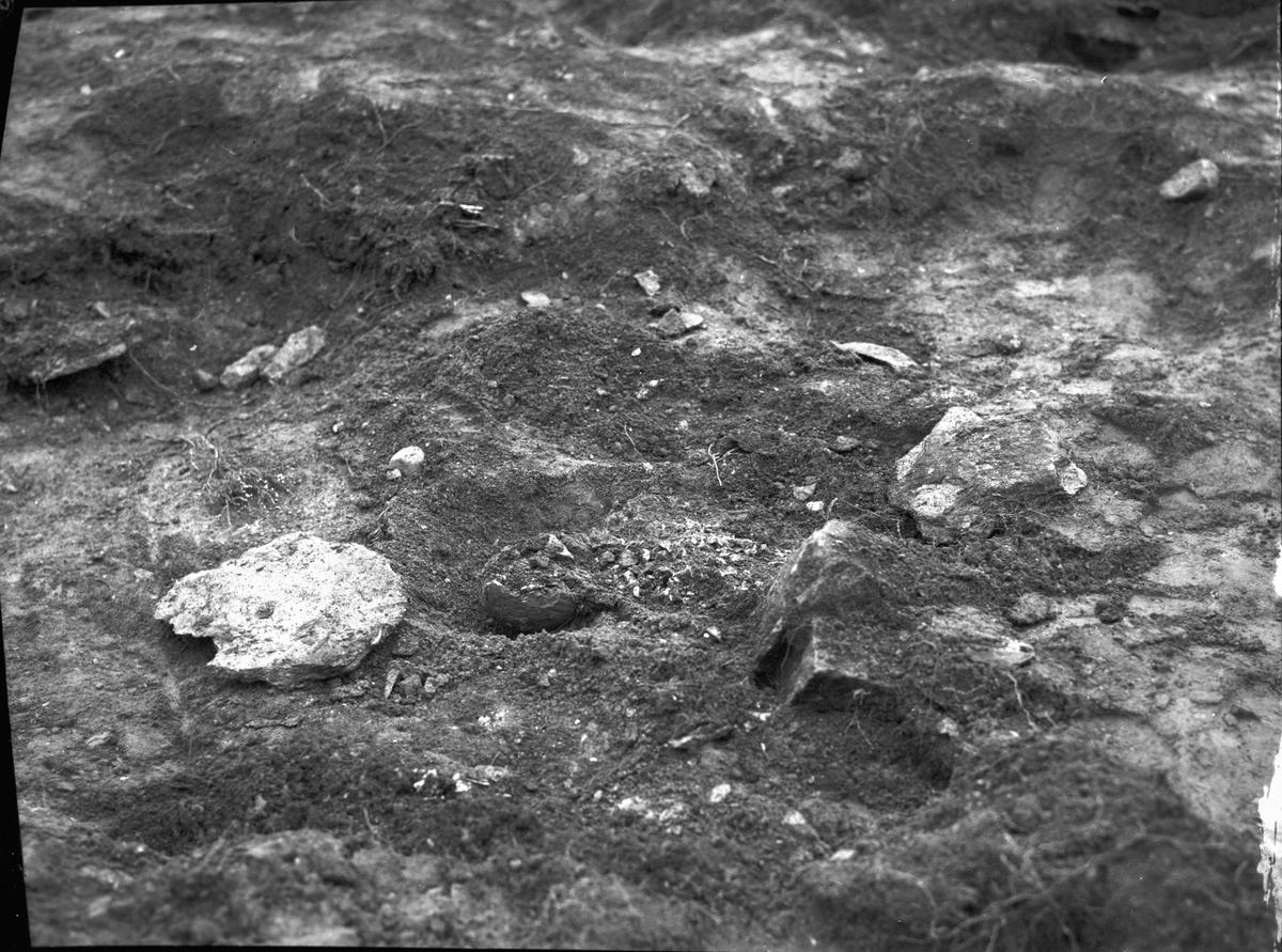 Grav 4 under utgrävning, i mitten synes en anhopning av brända ben och vid sidan därom en större skärva vidare ett vidbuktigt ornerat lerkärl.  S Hillingsäter  Färgelanda