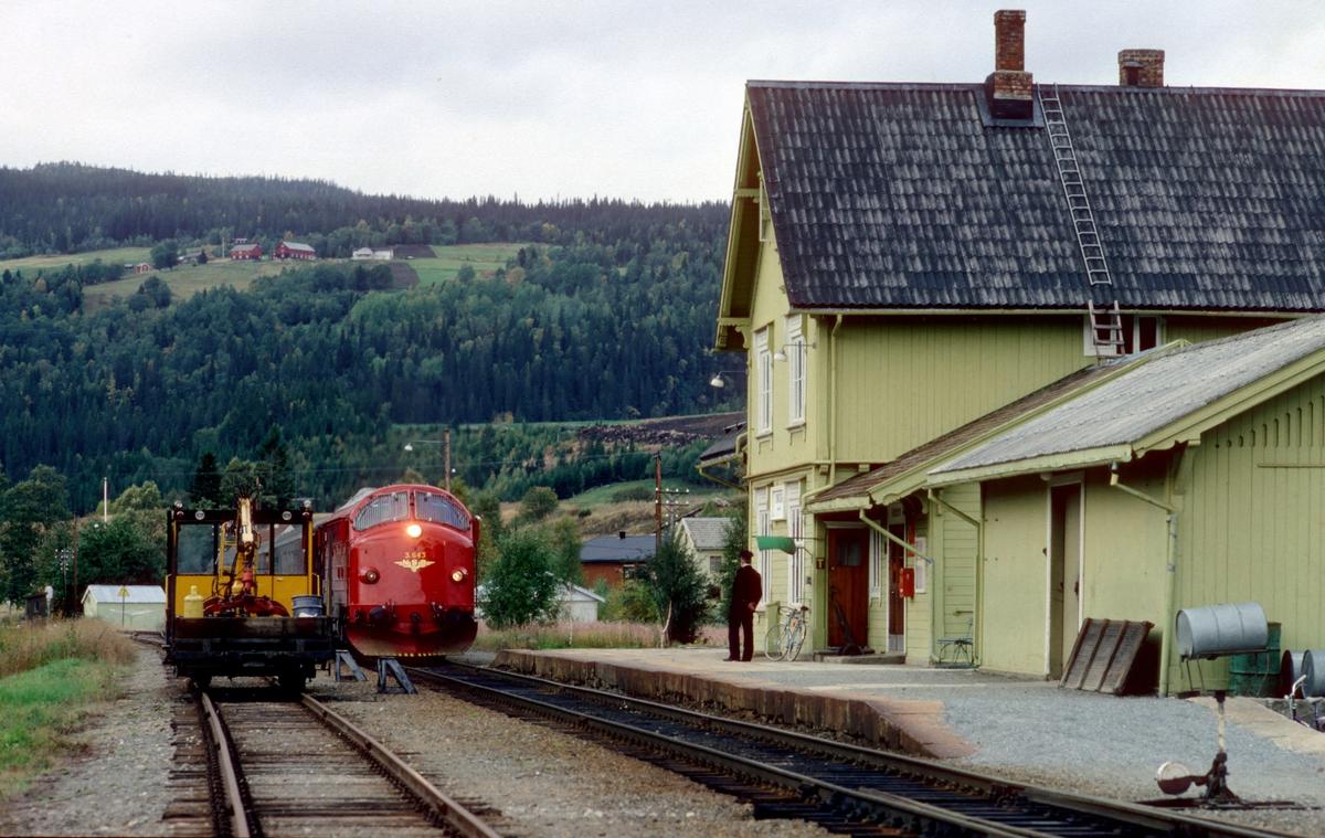 """Rørosbanens sørgående daghurtigtog 302 stopper ved Singsås stasjon. Togekspeditøren viser signal """"Passer"""" (grønt flagg), det var ingen påstigende. NSB dieselelektrisk lokomotiv Di 3b 643."""