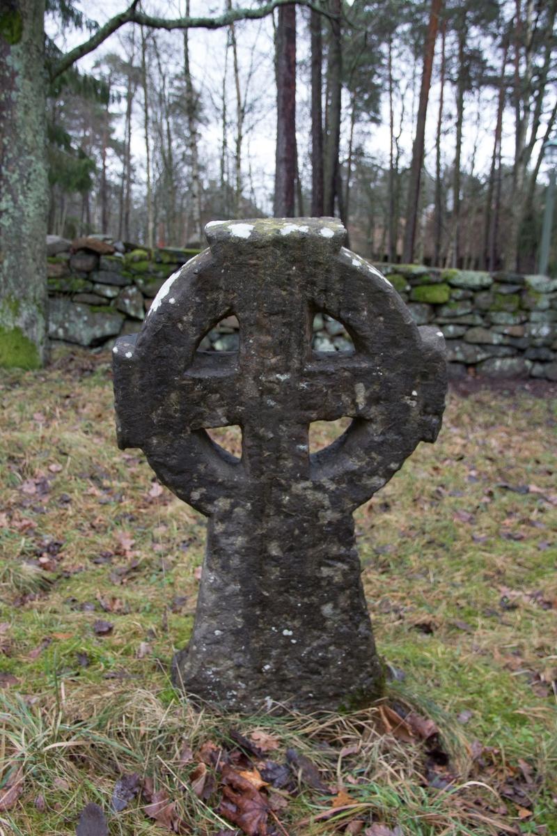 Gravsten, av sten, huggen, med ringkorsform. Inskrift BAS:ILD och årtalet 1769. (Delvis svårtytt.)