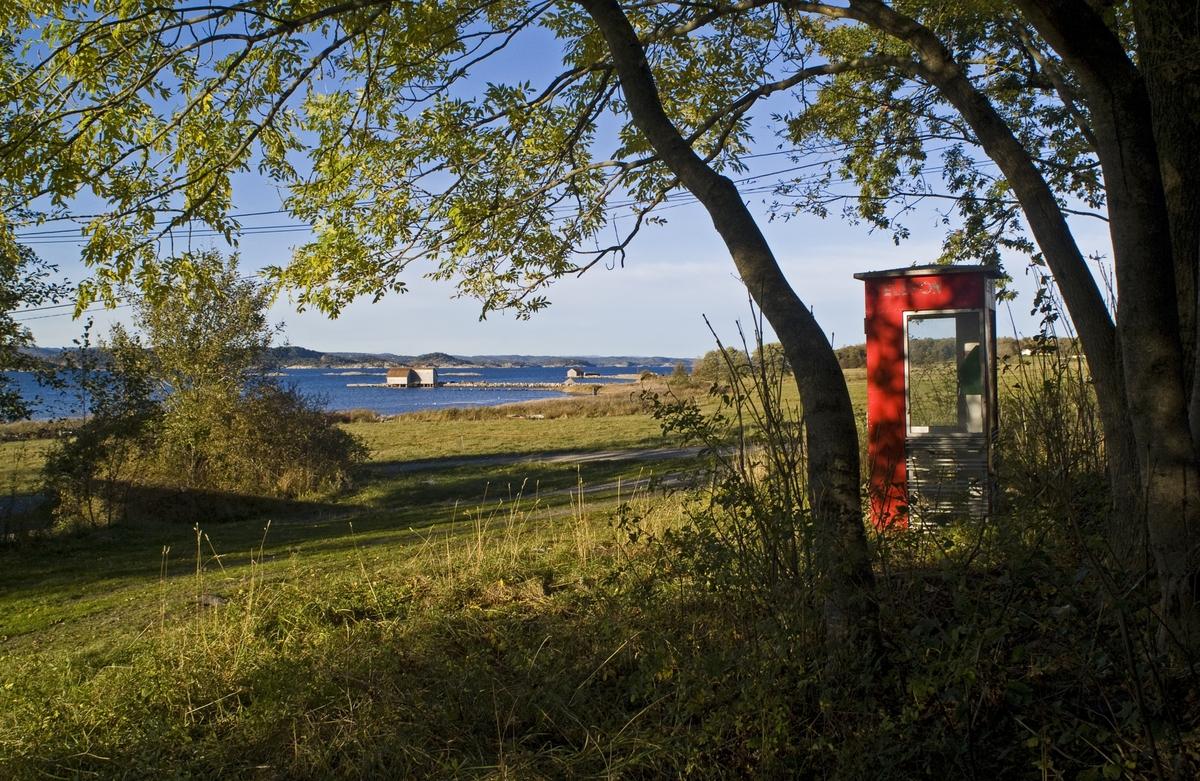 Denne telefonkiosken står på Jomfruland, og er en av de 100 vernede telefonkioskene i Norge. De røde telefonkioskene ble laget av hovedverkstedet til Telenor (Telegrafverket, Televerket. Målene er så å si uforandret.  Vi har dessverre ikke hatt kapasitet til å gjøre grundige mål av hver enkelt kiosk som er vernet.  Blant annet er vekten og høyden på døra endret fra tegningene til hovedverkstedet fra 1933. Målene fra 1933 var: Høyde 2500 mm + sokkel på ca 70 mm Grunnflate 1000x1000 mm. Vekt 850 kg. Mange av oss har minner knyttet til den lille røde bygningen. Historien om telefonkiosken er på mange måter historien om oss.  Derfor ble 100 av de røde telefonkioskene rundt om i landet vernet i 1997. Dette er en av dem.