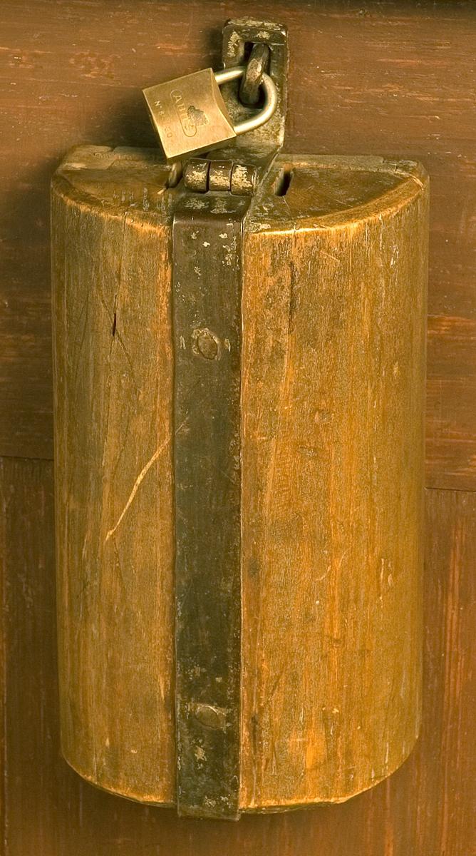 Fattigbössa av trä, brunmålad, halvcylindrisk med vertikalt metallband och hasp för låsning. (Modernt lås.) På ovansidan hål för att stoppa ner pengar. Fastsatt i kyrksalens främre bänkrad, fronten mot altaret.