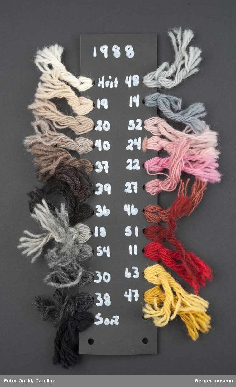 Svart pappremse med hull på hvers side, der garnprøver i forskjellige farger er knytet på. Garnfargene er nummerert med hvit penn på kartongen.