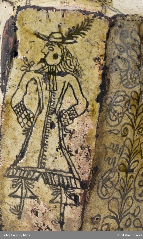Sjusidig flaska av lergods, engoberad, med ristad dekor med man i 1600-talsdräkt och växtornament. Se Bonge-Bergengren 1994, s 23.