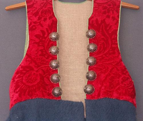 """Livkjol till Allbodräkten. Kjoldelen är sydd av ett blått grovt ylletyg vävt i liksidig kypert och ruggat på båda sidor, """"fris"""". Kjolen kantas nedtill av ett ljusblått sidenband och på insidan av fållen sitter ett randigt skoningsband av linne. Kjolen har en ficka på högersidan.Det fasta livstycket är sytt i reliefskuren röd schagg (yllesammet), kantat med grönt sidenband och fodrat med oblekt linnetyg. Tio silverbucklor är fastsydda framtill på livstycket.Allbodräkten är framtagen under 1980-talet efter studier av gammalt dräktmaterial i Nordiska Muséets arkiv. Allbodräkten är en mer historiskt förankrad dräkt än den traditionella Värendsdräkten. Se även pärm nr 126 om Allbodräkten och tidningsartikel från Smålandsposten lördag den 28 maj 1988."""