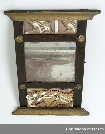 Spegel i Karl Johans-modell. Enkelt snickrad med ram av brunmålat trä med ursprungligt spegelglas. Krön och underdel utformade av guldbronserade hålkälslist  Spegelns övre och nedre fält dekorerade med mönstrad tapet som kanske skall efterlikna den typ av glasdekor som brukar finnas på s. k. glasmästarspeglar.  På ramen vid  spegelglasets hörn dekor av guldbronserade  fleuroner. Baksida med enkla bakstycken av trä, det övre en återanvänd kartongbit med reklamtext.
