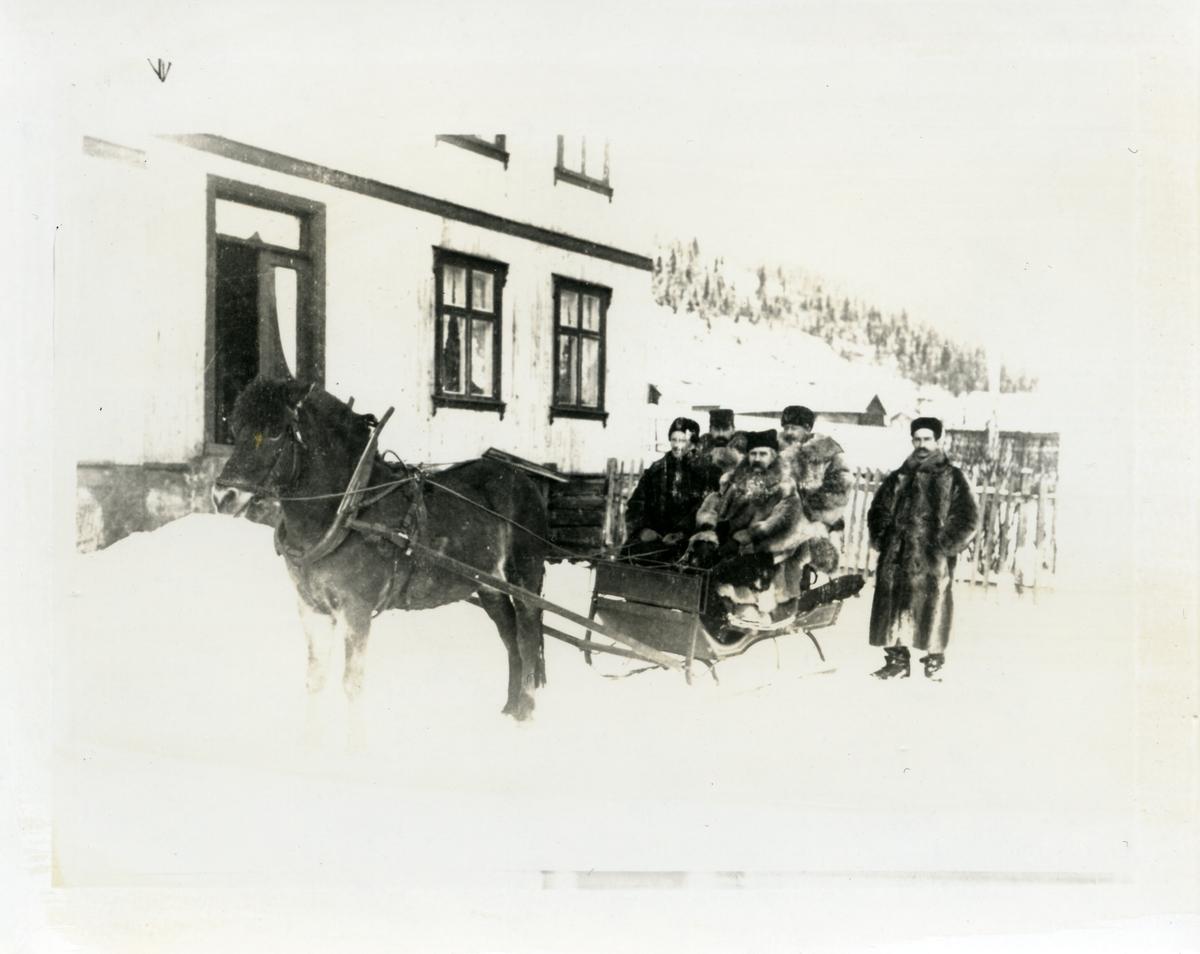 4 pelskledde menn sitter på en slede med hest foran. Bildet er tatt utenfor bygningen på Onstadmarken, Nord-Aurdal. Vinter og snø. Tatt mellom 1890 og 1895