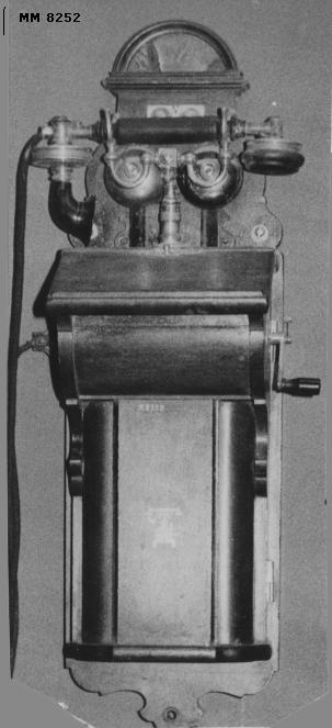 """Väggtelefon, modellen är troligen från slutet av 1800-talet eller början av 1900-talet. Apparaten är innesluten i en kåpa av mahogny. Klyka för handtelefonen är placerad överst på apparaten. Märkt överst: """"L.M. Ericsson & Co Patent Stockholm"""". Märkt på batterilocket: Firmamärket som utgöres av en bild föreställande en bordstelefon samt  texten: """"Trade Mark"""" Märkt kring bilden """"L.M. Ericsson & Co Stockholm""""."""