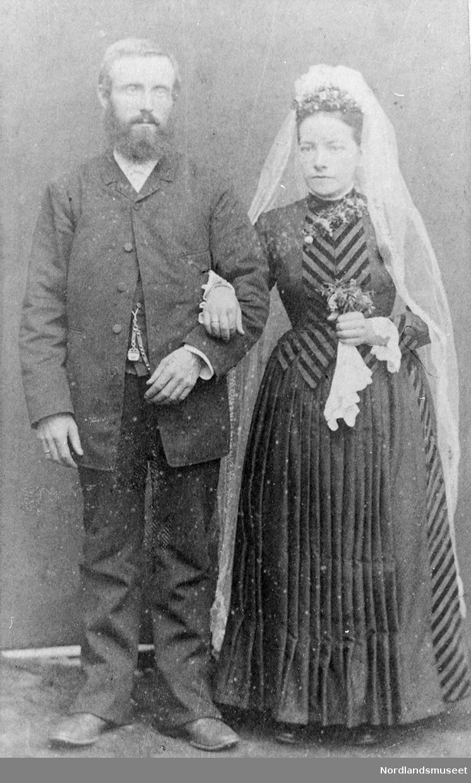 1 mann og en kvinne i helfigur. Mannen er kledd i mørk bukse, mørk jakke og lys skjorte. Han har skjegg. Kvinnen er kledd i mørk lang kjole og lyst langt brudeslør. I sin venstre hånd holder hun en brudebukett.