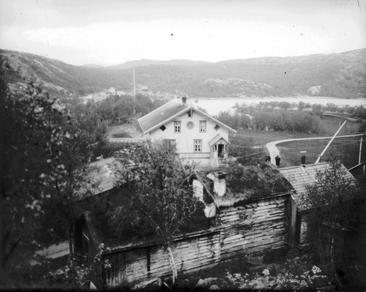 Et fotografi av gård i Elvenes. På forgrunenn tømmebyggninger, hus og uthuser, med torvtak. Selve gårde mitt på bildet.  Deler av en vippebrønn skimtes bak tømmerbyggningene.  Det står fire menn på veien ved det store huset.