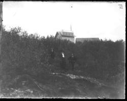 To kvinner og en mann står i skogen nedenfor et hus med alta