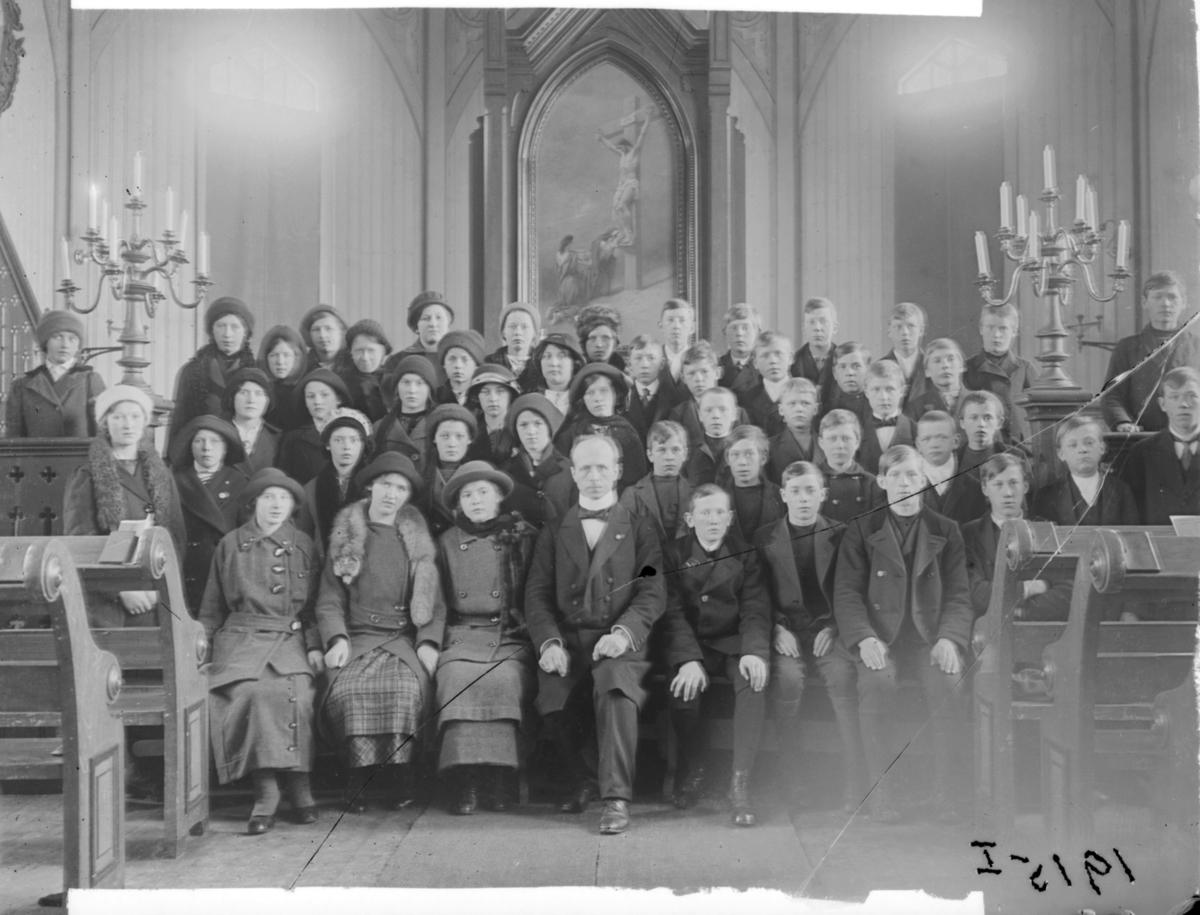 Konfirmanter, Vardø 1915. Bildet er tatt inne i kirka. Midt i første rekke presten Johan Oskar Grasmo