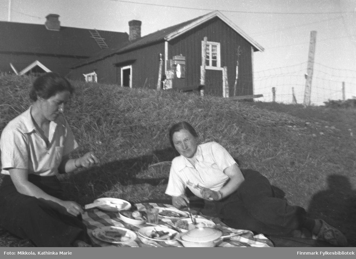 Middag utendørs, rett i nærheten av våningshuset på gården Mikkelsnes. Kvinnen til venstre: Stine Olsen, søster av Kathinka Mikkola. Kvinnen til høyre vet vi ikke navnet til, men hun var venninne av Stine