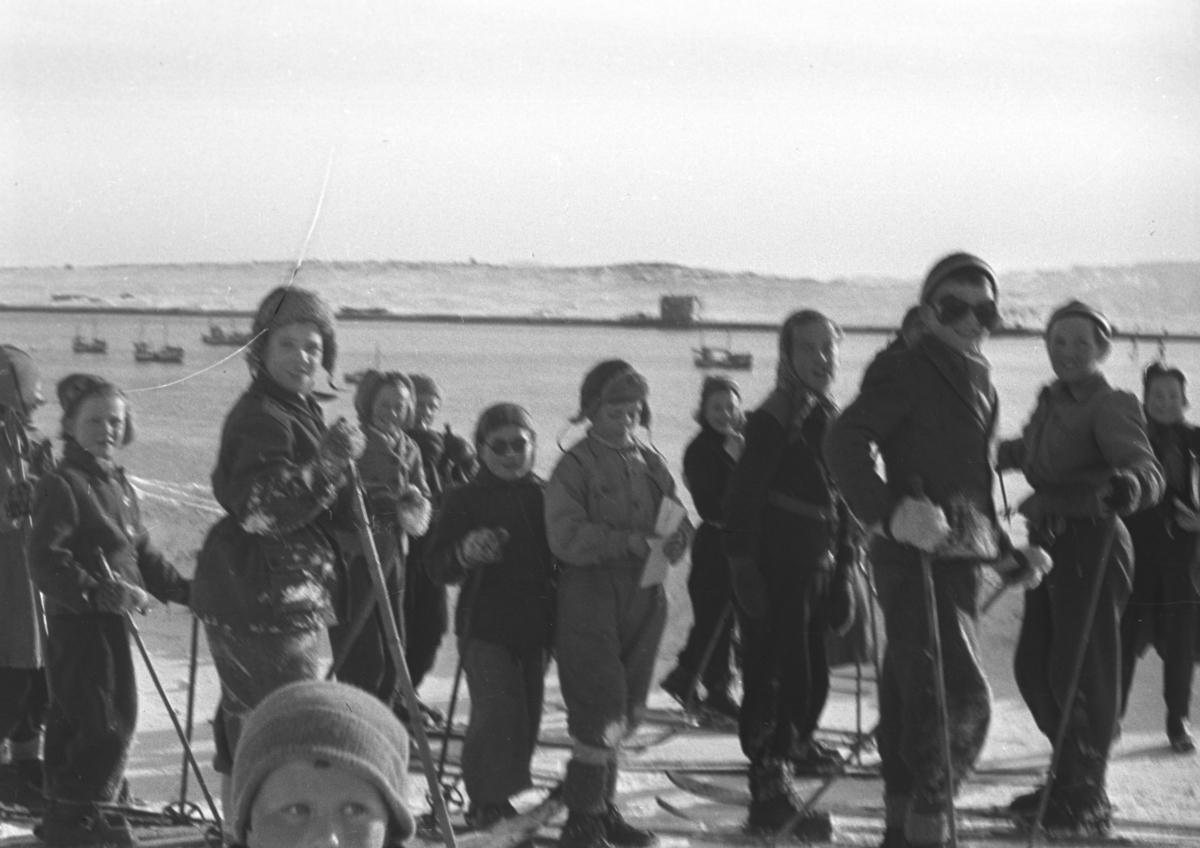 Mange barn deltar på skirenn i Vadsøs gater på 50-tallet. Havna med flere båter fortøyd ses i bakgrunnen. Personene er ukjent.