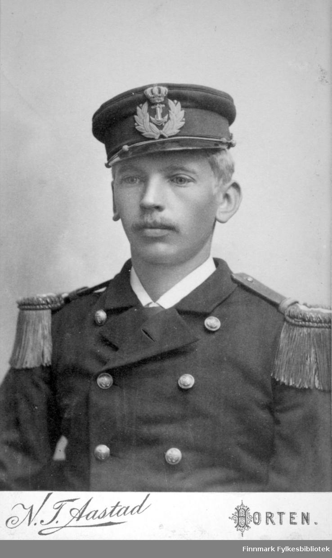Portrett av en ung mann i uniform. Uniformsjakka er mørk med store knapper og epåletter. Han har hvit skjorte under og uniformslue med marineemblem på hodet. Portrettet er tatt hos fotograf N. F. Aastad i Horten.