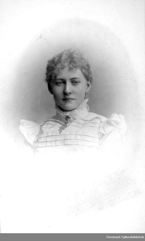 Portrett av en kvinne iført en lys bluse med noen striper foran og volanger.