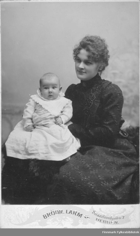Portrett av en dame i mørk kjole. Hun har et lite barn i lys drakt på fanget. Portrettet er tatt hos Hulda Bentzen i Bergen.