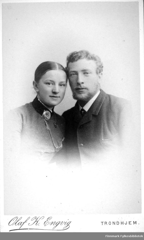 Portrett av to personer, en mann og en kvinne. Kvinnen har en mørk bluse og en brosje foran på kragen. En kjede henger fra halsen og nedover brystet. Mannen har en mørk dressjakke og hvit skjorte. Portrettet er tatt hos Olaf K. Engvig.