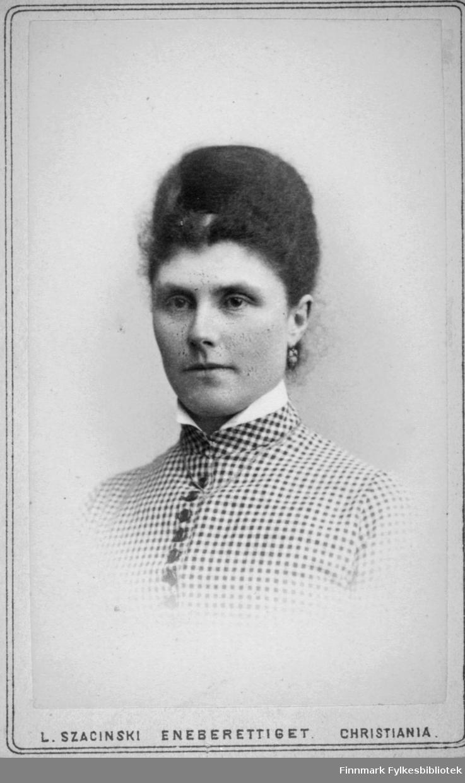 Portrett av en kvinne med oppsatt hår. Blusen hennes er lys med mørke prikker og knapper. En liten del av en lys krage ses rundt halsen og en øredobb henger i venstre øre. Portrettet er tatt hos kgl. hoffotograf L. Szacinski i Christiania.