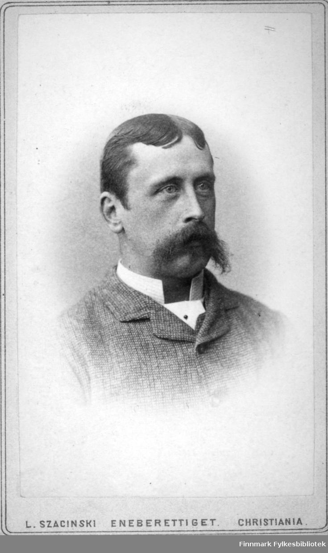Portrett av en mann i en ganske mørk ulldress med hvit skjorte under. Portrettet er tatt hos kgl. hoffotograf L. Szacinski.
