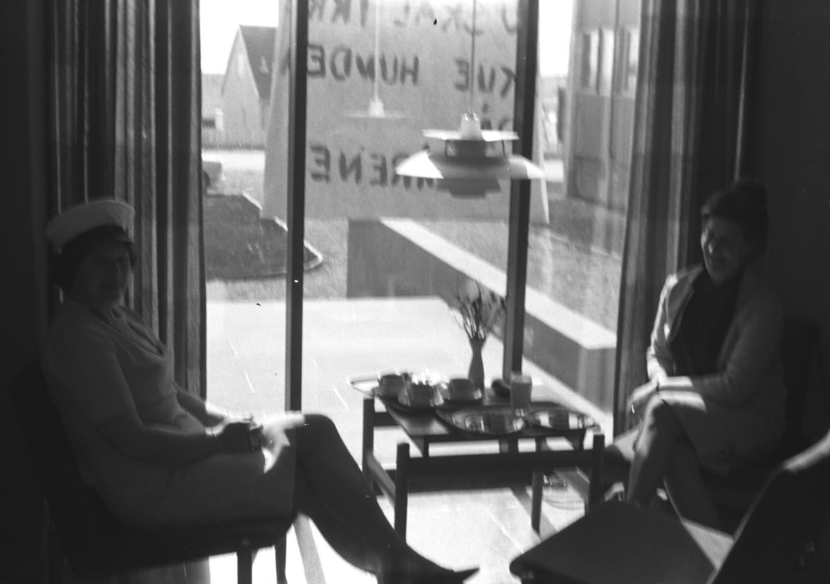 To damer sitter ved et lite bord. Sted og personer er ukjent.
