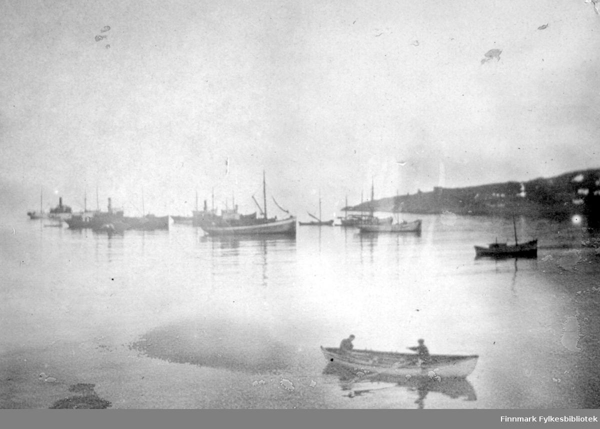En blikkstille Hasvik-fjord. Nærmest kamera ligger en liten, åpen båt med to personer i. Det ser ut som de fisker med garn. Lenger ute på fjorden ligger mange båter av varierende størrelse og form. Bakerst, til høyre ses et nes som stikker ut i sjøen. Det er noen snøflekker som tyder på at det er sen vår/tidlig sommer.