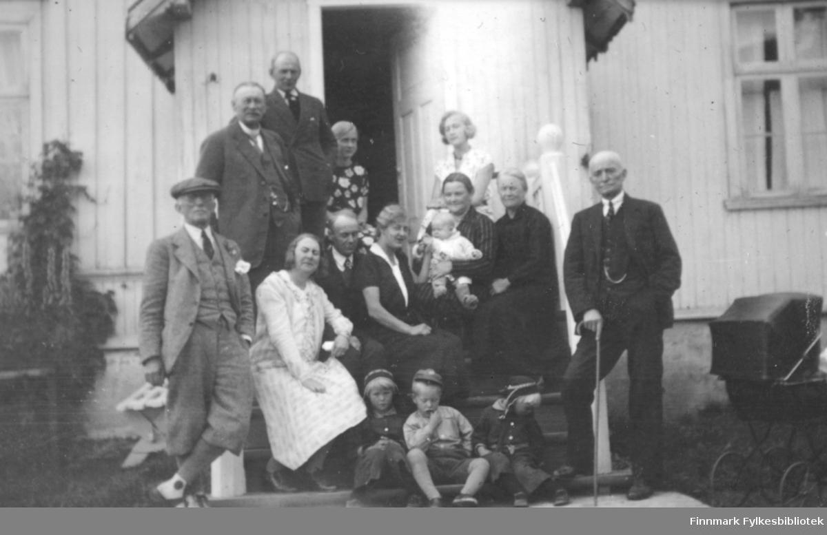 Mange personer poserer foran et hus. Fem menn som alle har dresser, hvite skjorter og slips. Herren til venstre har i tillegg sixpence på hodet og mannen til høyre holder i en spaserstokk. De fem damene har skjørt og hun i midten med mørks overdel holder et spedbarn i armene. Tre små gutter sitter helt foran og alle tre har caps på hodene og en av dem har kortbukser på. En ung dame står foran den åpne inngangsdøra og har mønstret overdel på seg. To vinduer ses på begge sider av vindfanget med gardiner i begge og et solid, hvitt trappegelender med utskjæringer ses bak mannen til høyre på bildet. En barnevogn med kalesjen oppe står helt til høyre i bildet. Helt til venstre ses en plante som er festet på veggen.