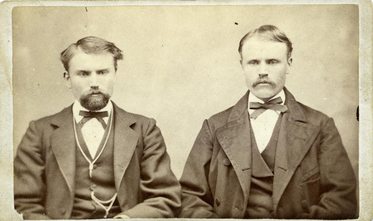 """To menn avbildet foran lerret. Mennene er ikledd dress og sløyfe. Tekst bakpå bildet: """" En erindring til Ole Andersen Qvale fra mig John K.T"""""""