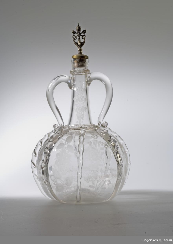 Siratflaske, dobbelhanket, gravert dekor i form av ranker og løv.        Metallkork er kommet til senere og hører ikke til flasken