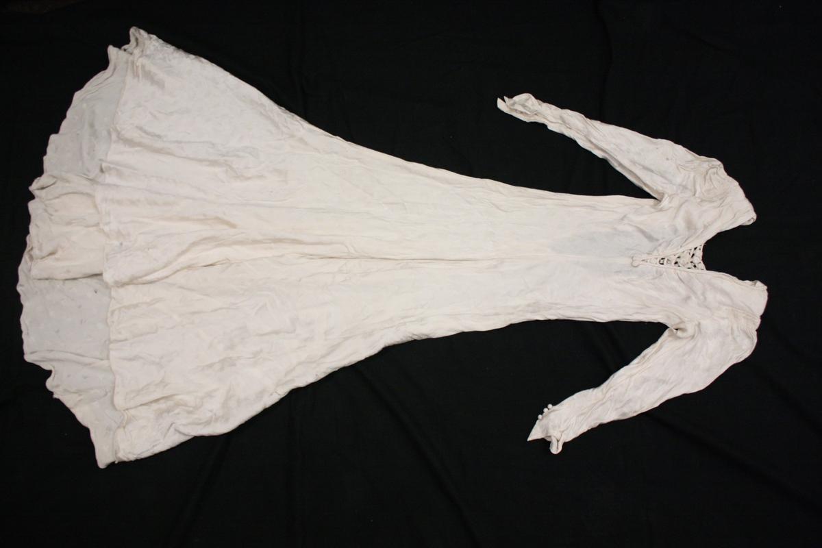 Brudekjole i hvitt silketekstil med glanset hvite prikker innvevet i tekstilet. Figursydd med slep. Knepping i ryggen der knappene er trukket i samme silketekstil. Øverst i ryggen er det også trykk-knapper. Brystet er V-skåret dekket til med en dekorutforming med snorer, broderi og små tekstilblomster. Nederst på ermene er det tekstiltrukneknapper. På skuldrene er tekstilet rynket.