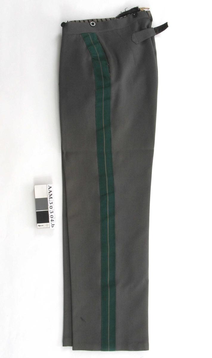 Rette ben med press, grønne striper på yttersiden. Spensel bak, lukking foran med knapper og hekte. En baklomme, lomme i begge sidesømmer. Knapper til bukseseler.