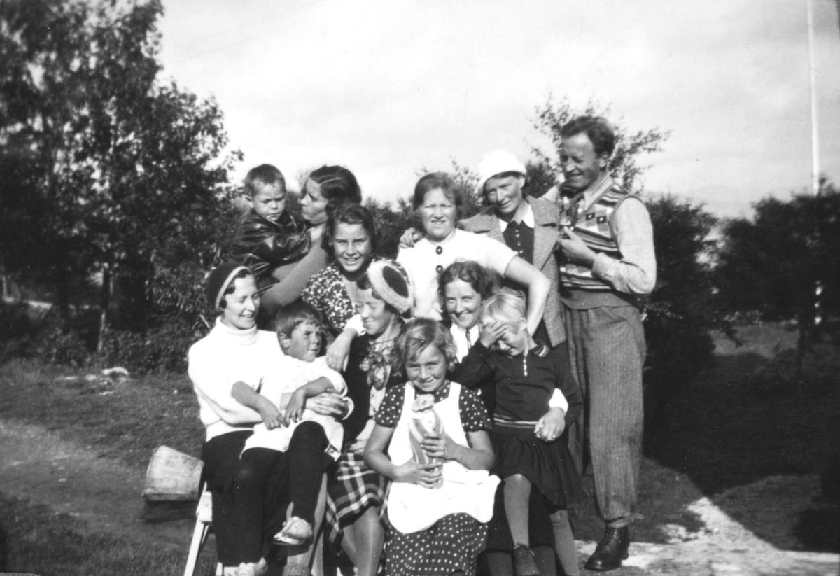 Gruppebilde fra familiealbummet til Leif Haugen. Det er tatt på Bjorøya i Bergen. Med på bildet er en mann, flere kvinner, og noen barn